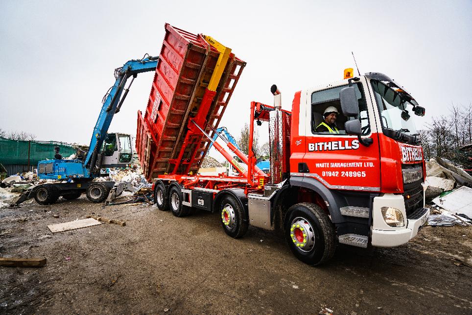 Bithells Waste Management photo of Palfinger Hookloader truck emptying waste container in yard